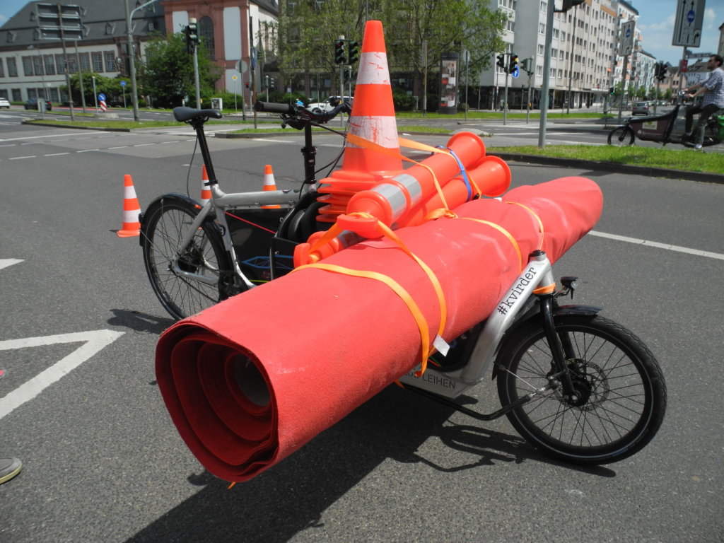 Ein Lastenrad, voll beladen mit Verkehrspylonen und einem breiten roten Teppich.