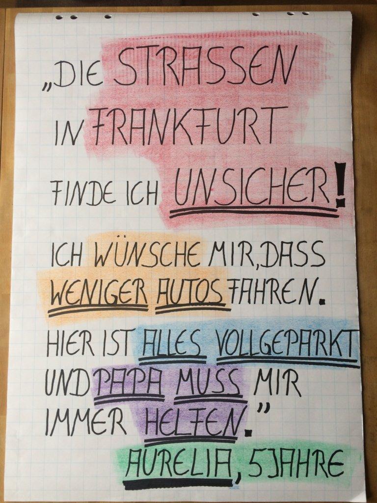 """Ein gemaltes Plakat, mit folgendem Text: """"Die Straßen in Frankfurt finde ich unsicher! Ich wünsche mir, dass weniger Autos fahren. Hier ist alles vollgeparkt und Papa muss mir immer helfen."""" (Aurelia, 5 Jahre)"""