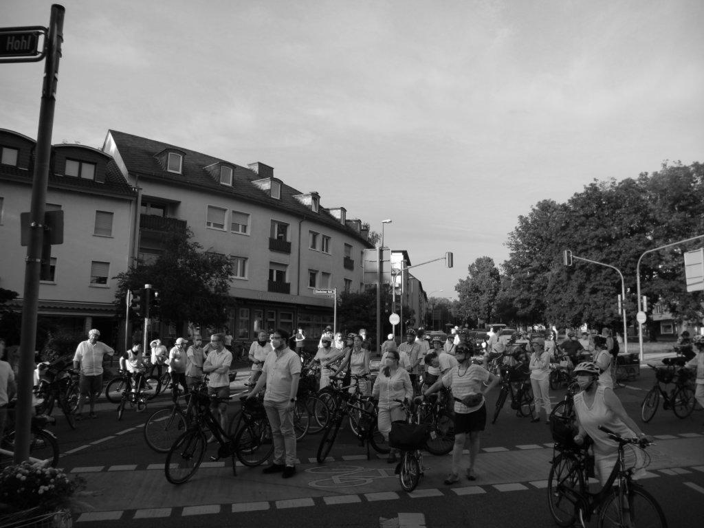 Die Teilnehmenden der Demonstration stehen zur Schlusskundgebung auf der Kreuzung am Ginnheimer Hohl; im Hintergrund die wartenden Autos.